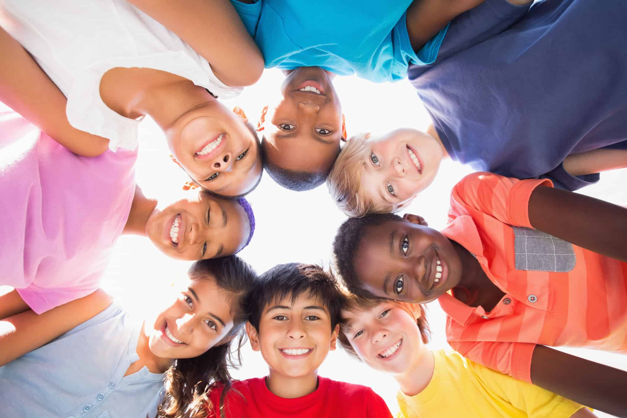 Group of smiling children in a circle staring down